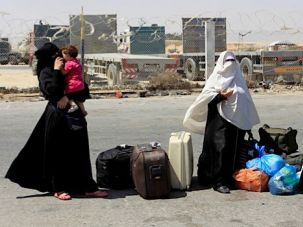 Waiting To Cross: Gaza women stand with their belongs outside of the Rafah border crossing in August, waiting for the checkpoint to be reopened.