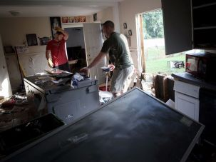 Two men help remove items ruined by Hurricane Harvey's flood damage from their friend's home in Dickinson, Texas. Dickinson was hit by Hurricane Harvey extremely hard, with major flooding in many areas of the city.