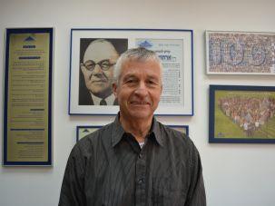 Yosi Ben Dov, the principal of the Reali school, in front of a photo of the school founder Arthur Biram.