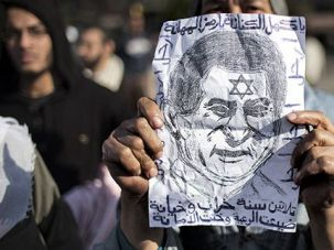 Egypt and Israel: An Egyptian protester holds up a caricature of President Hosni Mubarak with a Star of David on his forehead.