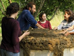 Working the Land: JFS Director Nati Passow (blue shirt) shows students how to work on a cob oven at Oz Farm in Mendocino County, Calif., in 2008.