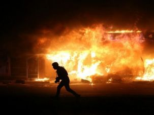 A man runs by a burning building in Ferguson during a demonstration protesting the grand jury's decision.
