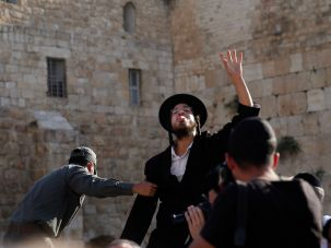 An Israeli policeman grabs an Ultra Orthodox Jewish man as he shouts slogans against the liberal Jewish religious group Women of the Wall.