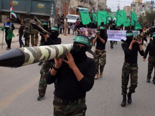 Palestinian militants from the armed wing of Hamas, carry mock-rockets.