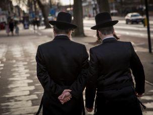 Two Hasidic men walk through the Stamford Hill neighborhood of north London.