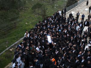 Ultra-orthodox Jewish mourners carry the body of one of the seven US children from the Sassoon family at the beginning of their funeral.