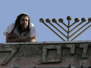 An Israeli settler stands next to a ritual candle-holder as he observes from the rooftop of the former house of the Palestinian al-Ghawi family -which is now inhabited by Israeli settlers — on September 4, 2015 during a demonstration in the mostly Arab neighborhood of Sheikh Jarrah in East Jerusalem against settlements.
