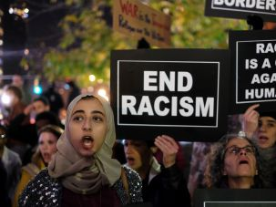 Human rights activists and people from Muslim community display placards during a demonstration in New York on December 10, 2015 in solidarity for Syrian and Iraqi refugees.