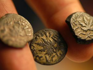 Chaim Gitler, curator of numismatics at the Israel Museum, shows coins dated to the ancient Jews' Great Revolt against Roman rule in 66 AD, decorated with vine leaves and the words in Paleo-Hebrew 'Freedom Of Zion' in the museum August 16, 2004 in Jerusalem, Israel.