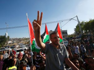 Palestinian journalist Mohammed al-Qiq, flashes the 'V' for victory sign as he arrives in the village of Dura near Hebron, in the West Bank, following his release from the Israeli Nafha prison on May 19, 2016.