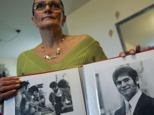 Remembering: Ilana Roman, wife of Israeli weightlifter Yosef Romano, one of 11 Israeli athletes murdered by Palestinian gunmen at the 1972 Olympic Games, shows her husband's official Olympic team portrait in his memorial photo album at her apartment January 24, 2006 in Tel Aviv, Israel.