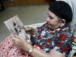 Frecha Amar, 84, from a Moroccan descent, poses with a picture of her baby, who she says was abducted in 1958, on June 29, 2016 at her home in Kfar Chabad, near Tel-Aviv.