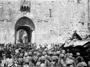 Israeli soldiers file past a burnt vehicle as they enter the Lions' Gate (or St Stephen's Gate), Old City of Jerusalem, Israel, June 11, 1967.