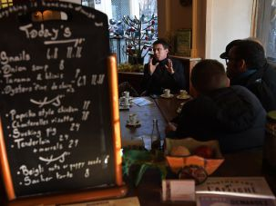 Manuel Valls at a Paris café. Note the English-language menu offering snails and bagels.