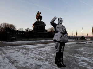 A demonstrator holds a cardboard cut-out depicting German dictator Adolf Hitler at the 'Deutsches Eck' memorial in Koblenz to protest right-wing politicians meeting there on January 21, 2017.