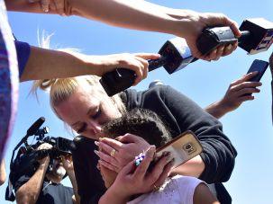 A mother embraces her child in San Bernardino, California, following a school shooting.