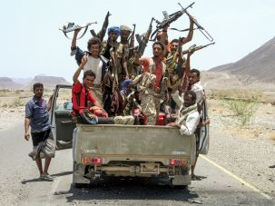 Yemeni fighters loyal to the Saudi-backed Yemeni president pose for a picture in the back of a Toyota pickup truck, raising their machine guns on April 15, 2017.