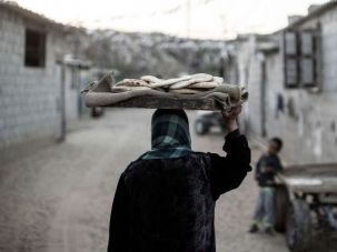 A Palestinian woman carries homemade bread next to their makeshift home in the Khan Yunis refugee camp in the southern Gaza Strip on April 19, 2017.