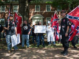 Ku Klux Klan members carrying Confederate flags display anti-Semitic signs