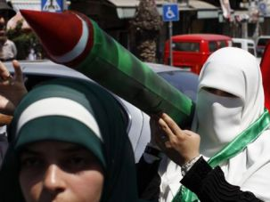 Uncompromising: A Palestinian woman carries a mock Qassam missile as she attends a rally in support of the Hamas movement following Friday prayers in Ramallah on August 8.