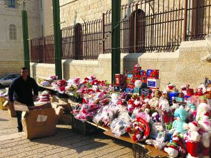 Bad Times for Business: A shopkeeper displays Christmas toys outside of the Nazareth bazaar, which was quiet in the days before the holiday.