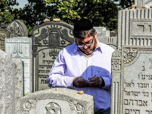 New York Pilgrimage: Baruch Amsel writes a note at the grave of the Brownsviller Rebbe.