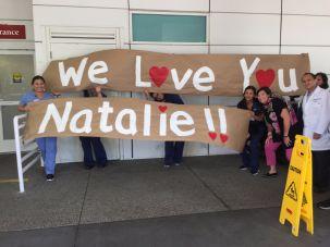 Natalie Grumet's coworker unfurling a welcome banner at Mission Hospital.