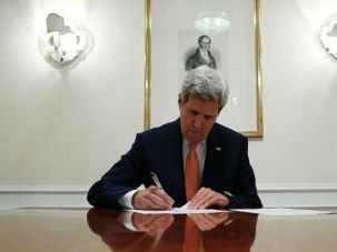 Secretary of State John Kerry signs the Iran nuclear deal.