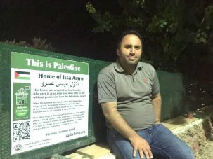 Issa Amro sitting in front of his home
