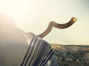 Man blowing shofar overlooking Jerusalem's Temple Mount.