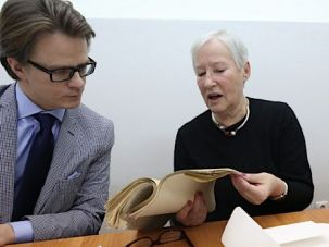 Literary Reunion: Ina Lancman (center) and Vita Serf leaf through the writings of their father, Naftali Herts Kon, at the Warsaw City Archives in March. Tomasz Koncewicz (left) is the lawyer who argued their case.