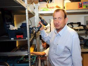 Tel Aviv mayor Ron Huldai holds a power drill at Tel v Kach.