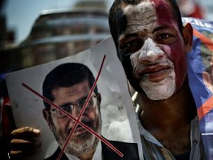 An Egyptian holds up posters during a protests against President Mohamed Morsi and the Muslim Brotherhood as they join thousands at Egypt?s landmark Tahrir square on June 30 in Cairo.