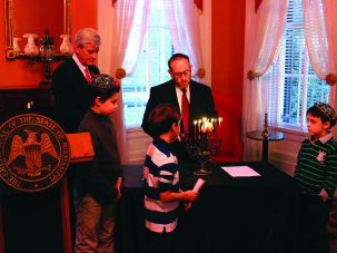Southern Comfort: Rabbi Jeffrey Kurtz-Lender of Beth Israel Congregation in Jackson, Mississippi, lights a hanukiah in the office of Mississippi Governor Phil Bryant as Bryant (left) and three children from the Jewish community look on.