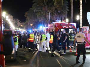 Police officers, firefighters and rescue workers are seen at the site of a terror attack in Nice, France on July 15, 2016.