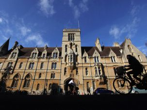 People bicycle past a building on an Oxford University campus.