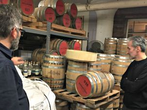 Daric Schlesselman of Van Brunt Stillhouse shows his barrels to Samuel Freedman.