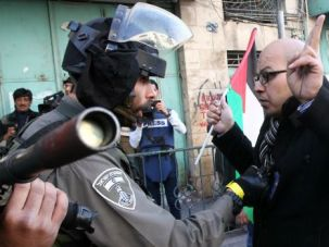 An Israeli border guard talks to a Palestinian protester during a demonstration against the visit of Israeli President Reuven Rivlin to attend the dedication ceremony of the Hebron Heritage Museum.