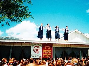Fiddlers on the Roof: Four 11th-grade girls announce the beginning of color war, one of the many competitive activities at Machne Rav Tov in Kerhonkson, Ulster County. More than 1,000 girls from the insular Satmar communities in Williamsburg and Monroe attend the camp each summer.