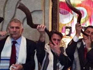 Rabbi Ron Kaplan (first to right) blows shofar at Temple Har Shalom.