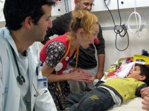 Bringing Laughter: Medical clown Penny Chanucah helps a young patient feel more comfortable prior to a procedure.