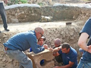 Archaeologists pull the ancient toilet out of the shrine at Tel Lachish.