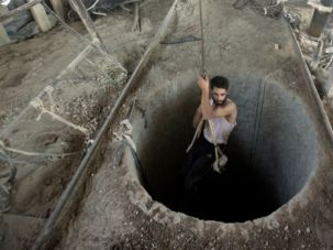Subterranean: A Palestinian man is lowered into a smuggling tunnel beneath the Gaza-Egypt border, in the southern Gaza Strip, on September 11, 2013.