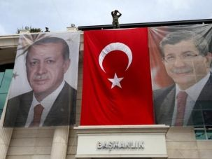 A special forces police officer takes security measures as he stands on top of a building where the portraits of Turkey's President Tayyip Erdogan (L), Prime Minister Ahmet Davutoglu and a Turkish flag are displayed in Istanbul, Turkey, June 3, 2015.
