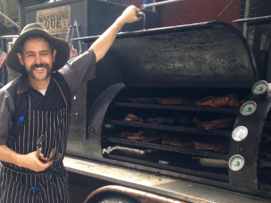 Last year's Brisket King, Ari White, poses in front of his smoker at a street fair in Manhattan.