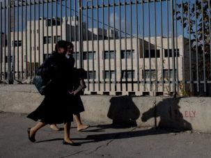 Women walk by Pnunim seminary in Jerusalem, one of several school at which a rabbi is accused of molesting girls.