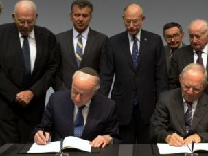 Done Deal: German Finance Minister Wolfgang Schaeuble, right, and Julius Berman, chairman of the Conference on Jewish Material Claims Against Germany, sign an agreement to expand benefits to Holocaust survivors.
