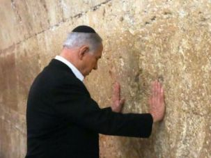 Israeli Prime Minister Benjamin Netanyahu prays at the Western Wall ahead of his trip to the U.S.