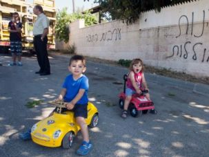 Shameful Hatred: Children play in the shadow of anti-Arab graffiti in an Israeli village that is seen as a symbol of peaceful coexistence.