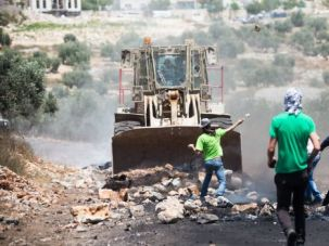 Need To Know: Palestinian protesters try to block Israeli bulldozer on the occupied West Bank.